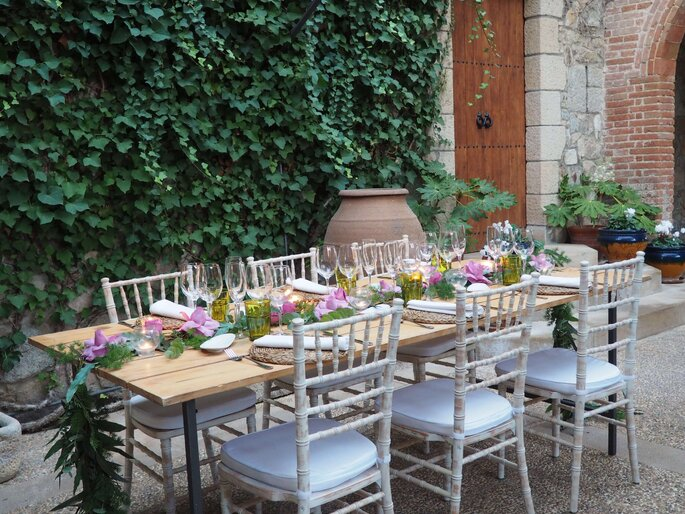Table de banquet installée en extérieure devant une façade de lierre, joliment décorée