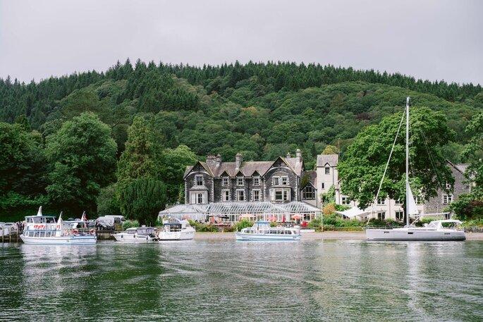 Une somptueuse demeure, probablement un lieu de réception, située au bord d'un lac, Derrière elle s'étend une grande forêt.