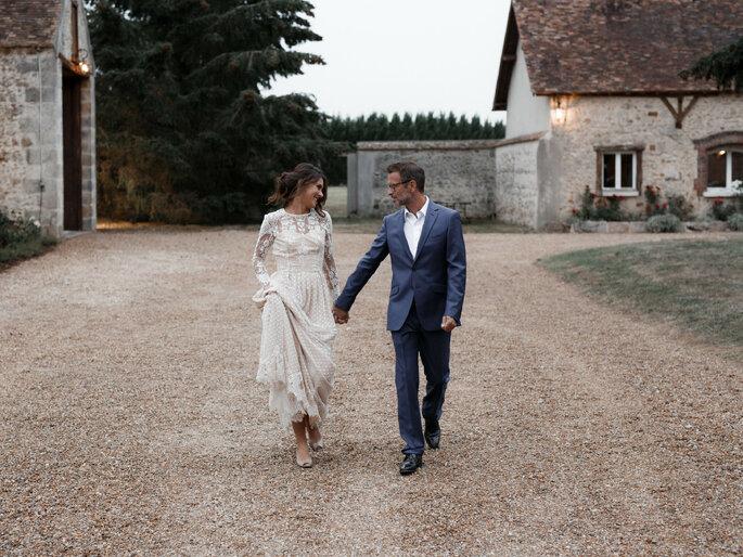 Un couple qui s'avance main dans la main dans la cour du Domaine de la Thibaudière