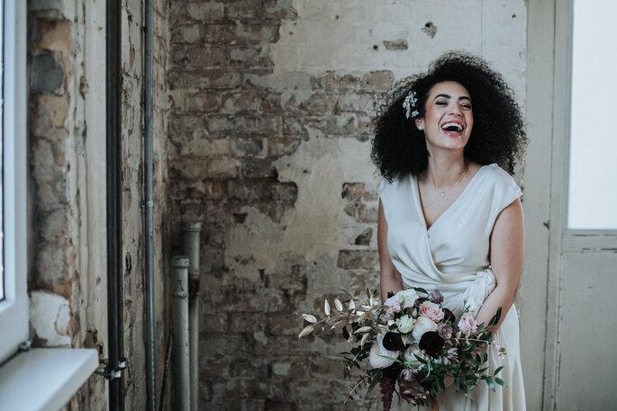 Porträt der lachenden Braut im weißen Kleid mit Brautstrauß, organisiert von Freakin' Fine Weddings.