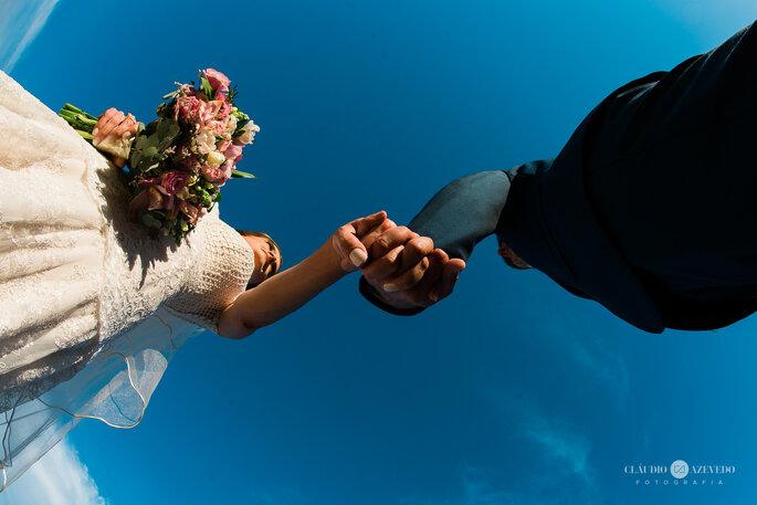 Noivos de mãos dados após troca de alianças