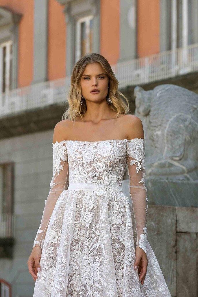 Berta Bridal vestido de novia en corte princesa con hombros descubiertos, escote palabra de honor, mangas largas de efecto tatoo, decorado con bordados florales.