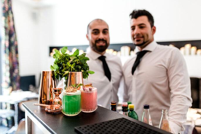 Zwei farbige Cocktails von Two gus and a bar auf dem Tresen. Im Hintergrund sind die beiden Gründer zu sehen.