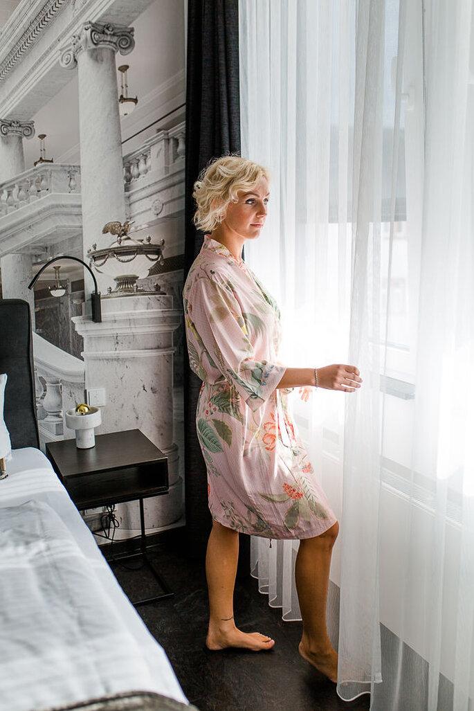 Die Braut steht im Hotelzimmer nachdenklich am Fenster und trägt einen Morgenmantel in zarten Rosétönen.
