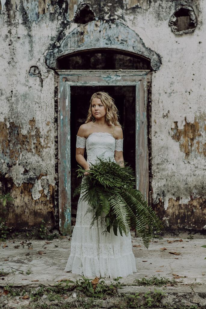 Die Braut steht vor einem alten Gebäude und hat Farn in der Hand.