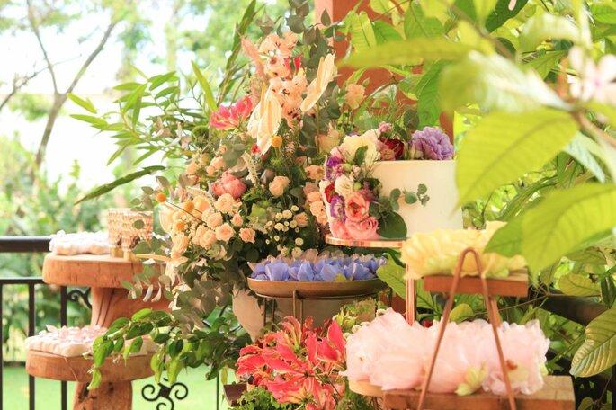 Mesa de doces com flores coloridas