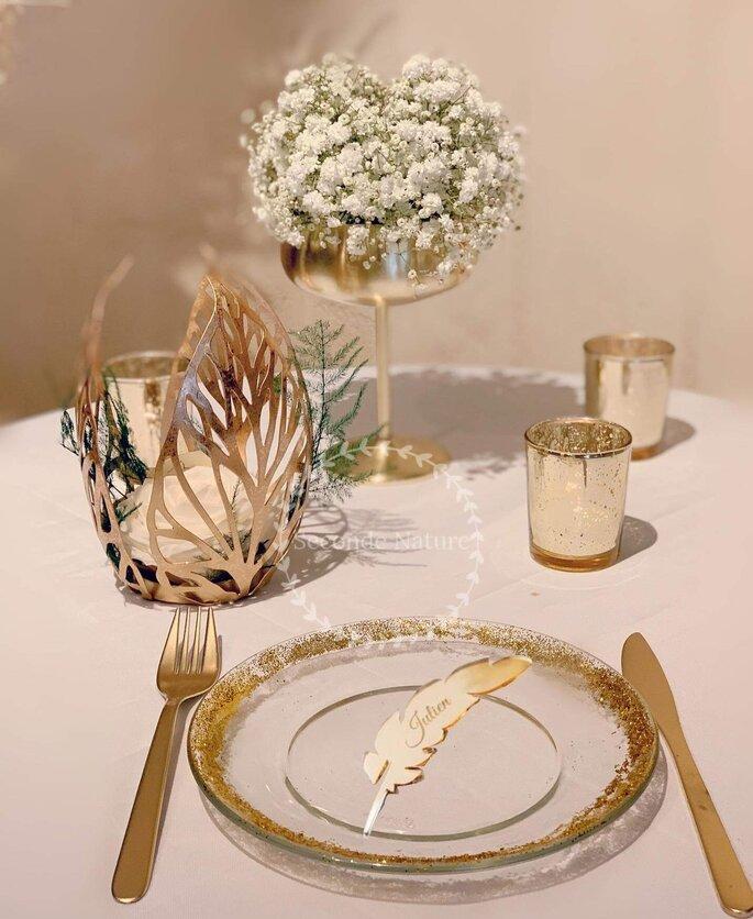 Décoration de mariage dorée avec un bouquet rond en œillets blanc