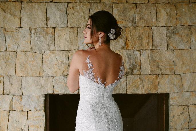 Novia con vestido escote en la espalda y peinado recogido con broches