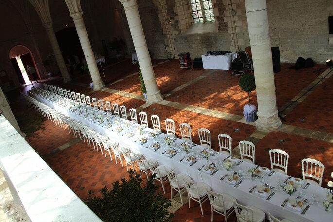Une immense table décorée dans une abbaye pour un dîner de mariage