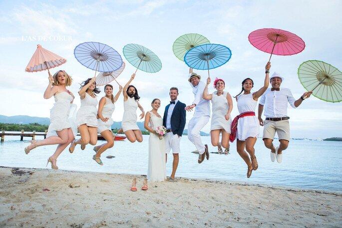 Des mariés posent devant l'océan avec leurs invités qui tiennent des ombrelles de couleur