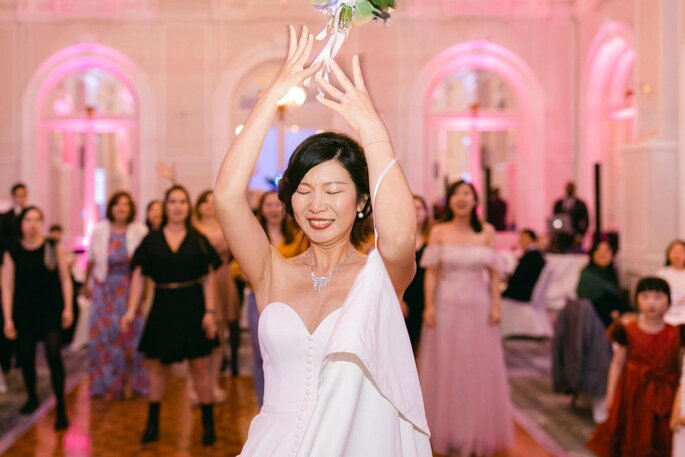 La mariée lance son bouquet à ses invitées.