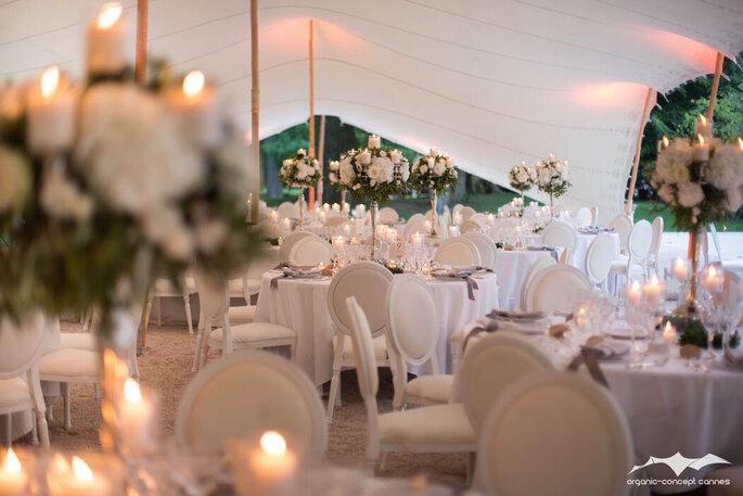 Tables de réception de mariage fleuries et décorées de bougies, sous une tente élégante