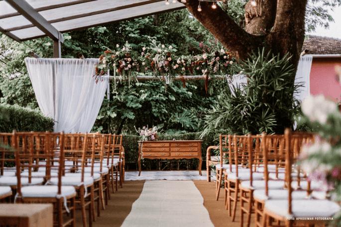 Cerimônia decorada para mini wedding, com pergolado florido, tapete claro, cadeiras Tiffany