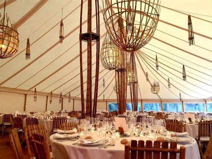 L'intérieur d'une tente en bambou de réception, aménagée pour un mariage bohème chic ou champêtre