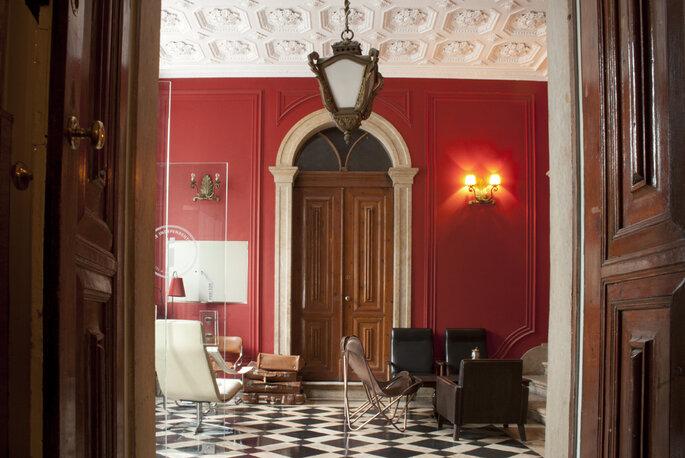 Foto da porta de madeira, em parede vermelha no Hostel The independent, em Lisboa.