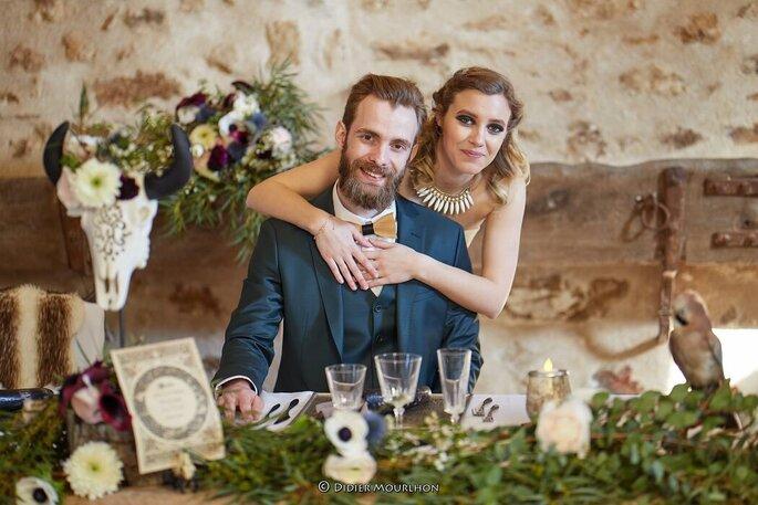 Un couple de mariés à sa table décorée de fleurs et de végétaux dans un esprit très bohème-chic.