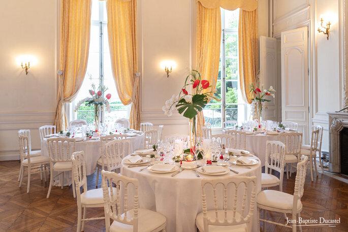 Tables dressées pour un mariage, avec des fleurs rouge, un sol en parquet, une jolie salle de réception au Château de Santeny