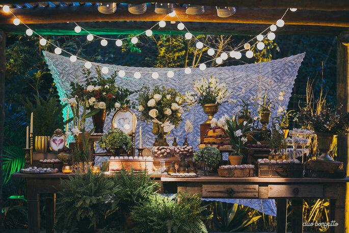 Mesa de doces com fundo em renda, varal de luzinhas e flores brancas