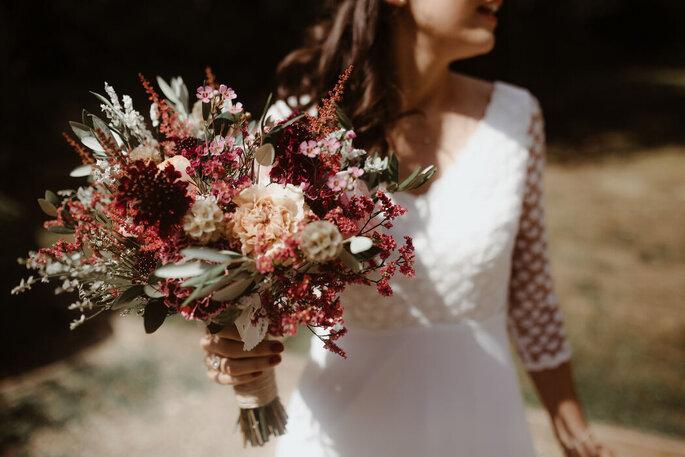 Une mariée tient un bouquet dans sa main, garni de fleurs fraiches et séchées aux couleurs automnales.