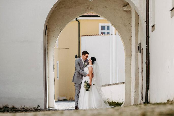 Das Brautpaar Marina & Tim küsst sich unter einem Torbogen, Foto von Hüttner Fotografie.