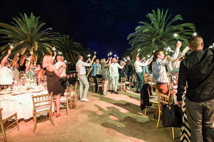 Les invités d'un mariage au Maroc acclament les mariés debout au cours de la réception en extérieur