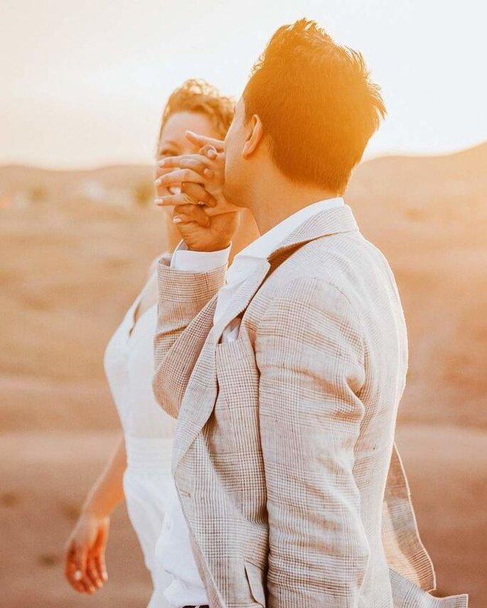 Deux mariés se tiennent par la main dans le désert sous la lumière du jour qui décline - meilleure photographie de mariage