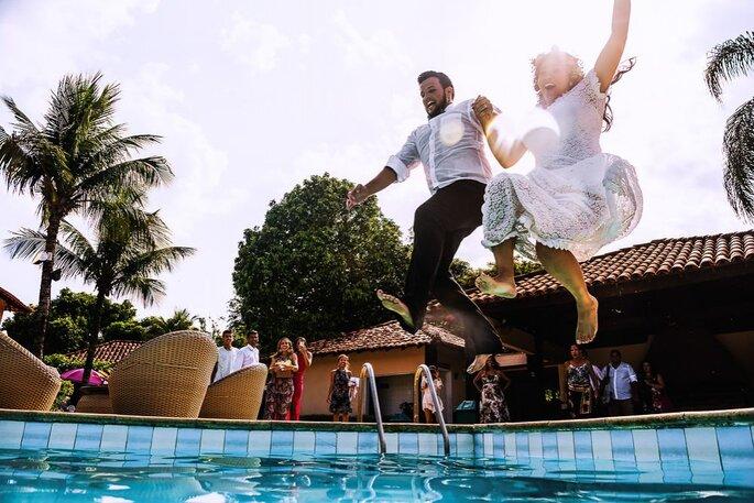 Noivos pulando na piscina