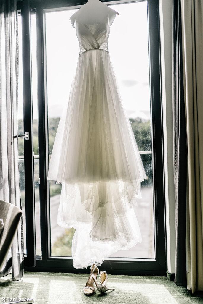 Kleid der Braut hängt vor Fenster