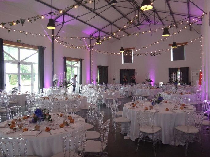 Salle de réception du Nomade Lodge décorée pour un mariage avec des guirlandes lumineuses et une lumière rose tamisée