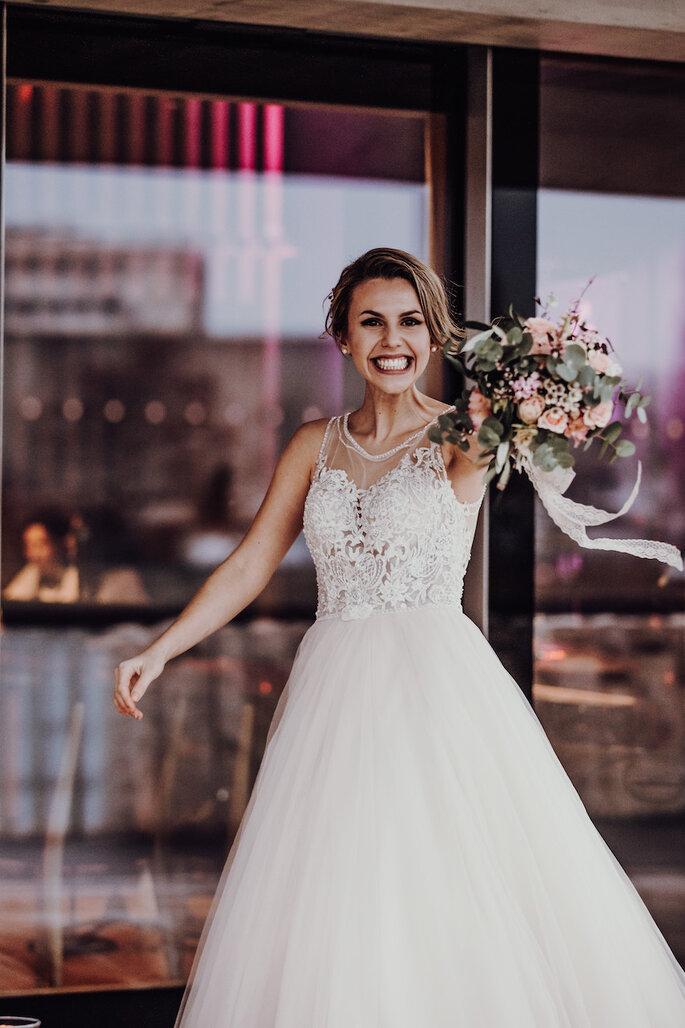 Eine Braut hält bei der Hochzeitsmesse Bridal Teamtime einen Brautstrauß in der Hand und lächelt.