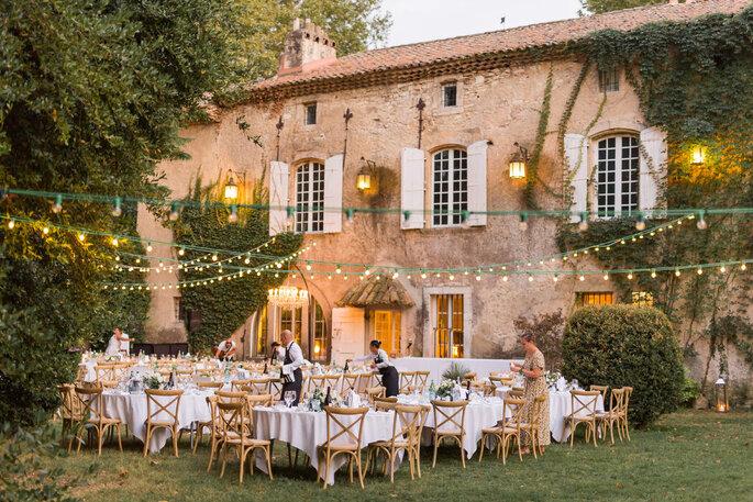 Une table dressée dans un jardin pour le dîner de réception, décorée par des guirlandes lumineuses