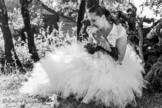 Une mariée photographiée avec un volatile du spectacle d'Esprit Fauconnerie