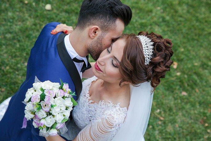 Un couple de mariés enlacé dans un champ