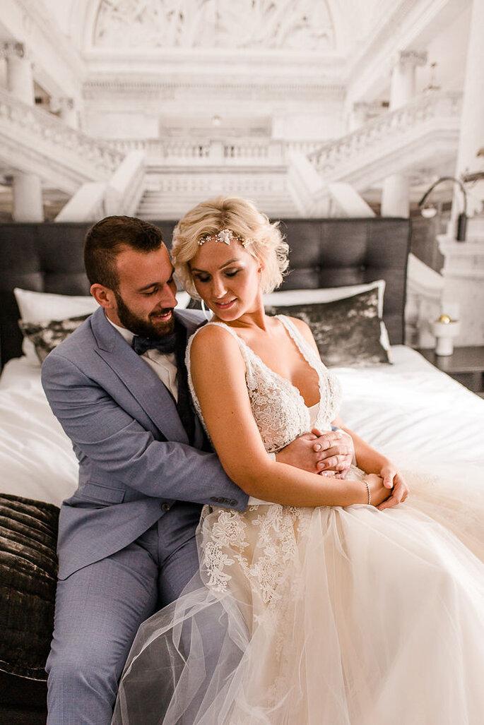 Das Brautpaar sitzt gemeinsam auf dem Bett und hält sich eng umschlungen. Beide tragen Outfits von Enzoani.