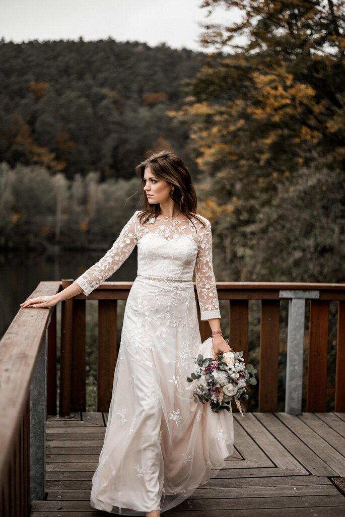 Eine Braut steht an einem Holzgeländer und schaut in die Ferne.