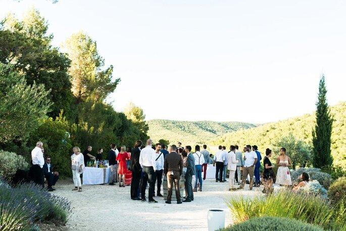 Les invités d'un mariage profitent du parc du lieu de réception en Provence