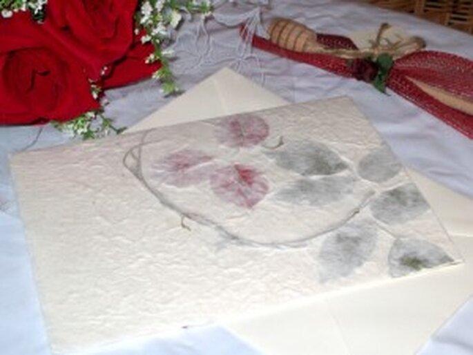 Invitación clásica sobre pasta de papel natural decorado con tallos y pétalos rojos.