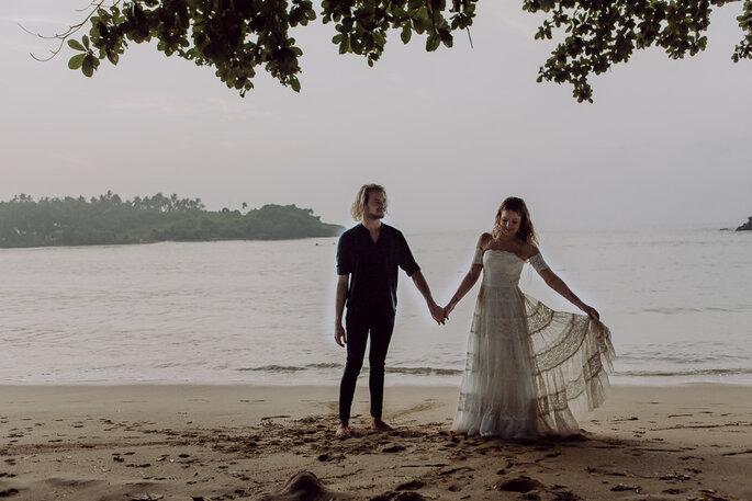 Das Brautpaar steht am Strand und hält sich an den Händen.