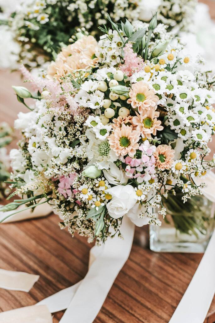 Une composition florale mélangeant des fleurs de couleurs blanches et pêches.