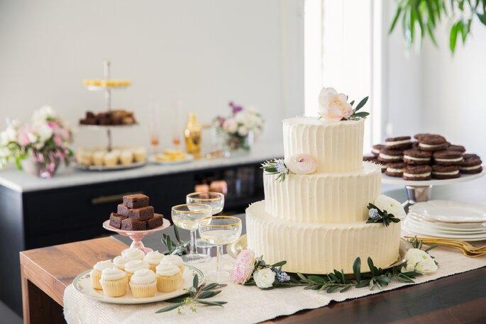 Ein Dessert Tisch mit Törtchen und Hochzeitstorte.