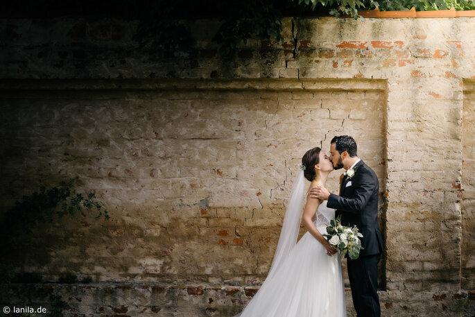 Brautpaar küsst sich vor Steinmauer