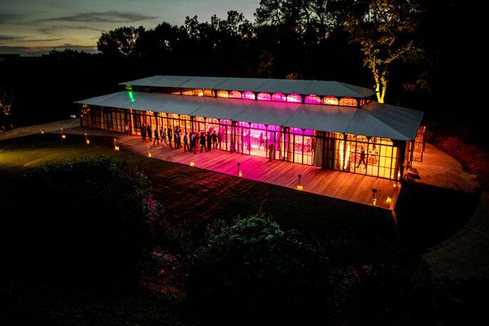 Une orangerie illuminée la nuit lors de la célébration d'un mariage