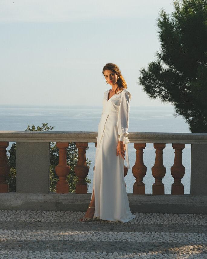 Une mariée poste dans sa robe à manche longue fluide et dotée d'une fente devant une balustrade près de la mer