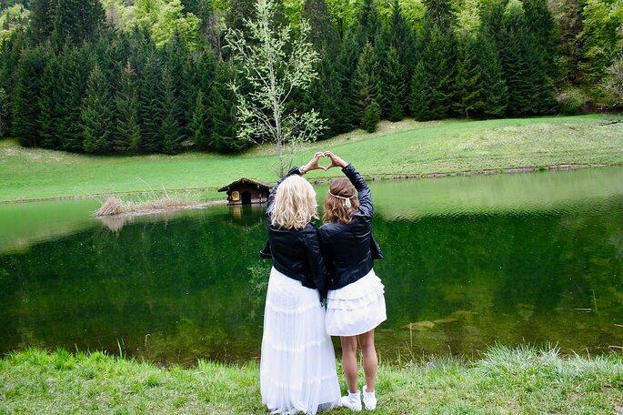 Deux fillettes enlacées faisant un coeur avec leurs mains devant un lac, en pleine nature