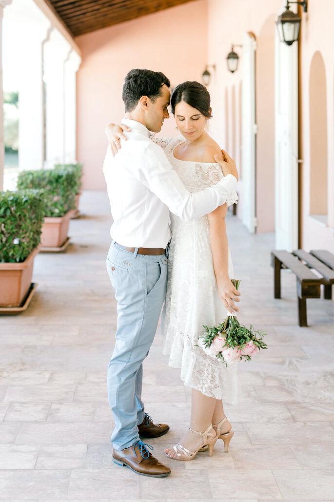 Un couple de mariés s'enlace devant le Pavillon Sully. La mariée tient son bouquet de fleurs à la main.