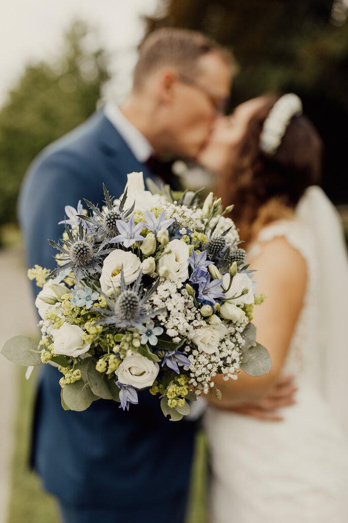 Brautstrauss, im Hintergrund Brautpaar