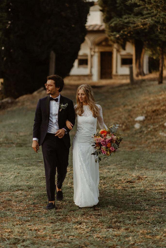Un couple de mariés se promène dans le parc du lieu de réception de leur mariage