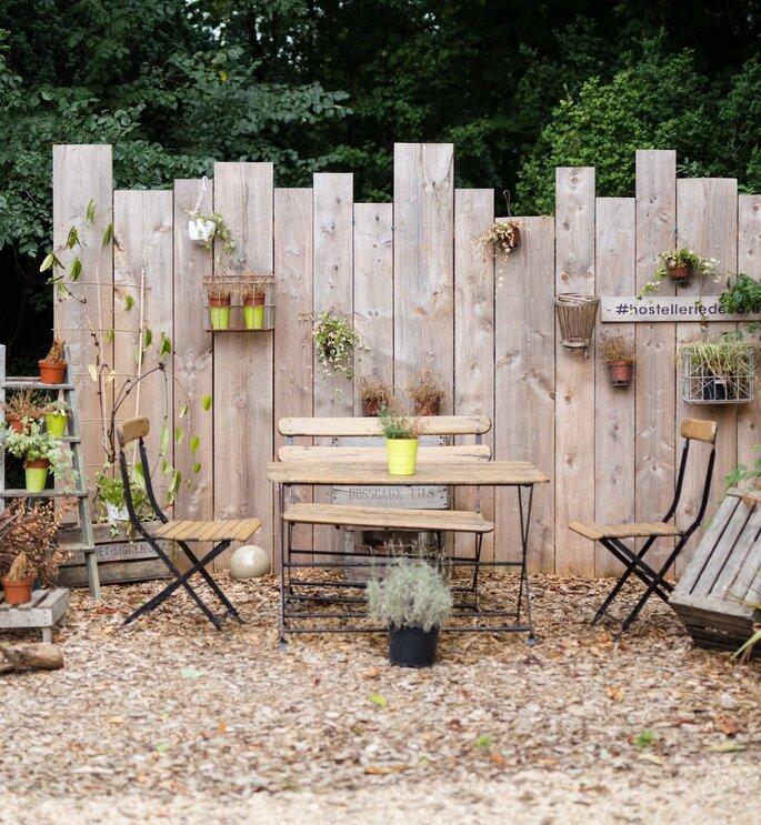 Un espace bucolique où s'assoir en extérieur, derrière des palissades