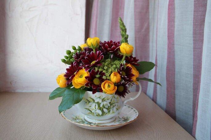 Arreglo de mesa con flores amarillas y moradas en taza de porcelana