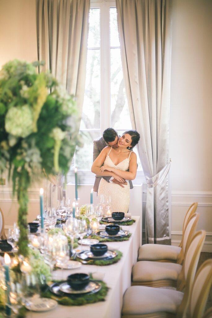 Deux mariés enlacés dans salon avec une table dressée et décorée devant eux
